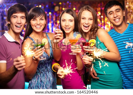 Portrait of joyful friends toasting at New Year party - stock photo