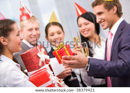 Portrait of joyful girl in birthday cap holding heap of giftboxes given by her colleagues - stock photo