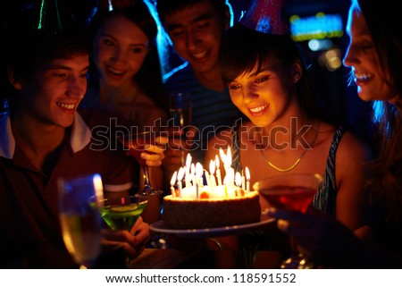Portrait of joyful girl looking at birthday cake surrounded by friends at party