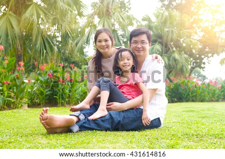 Portrait of joyful happy Asian family at outdoor park during summer sunset.