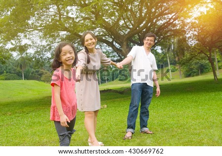 Portrait of joyful happy Asian family playing together at outdoor park during summer sunset.