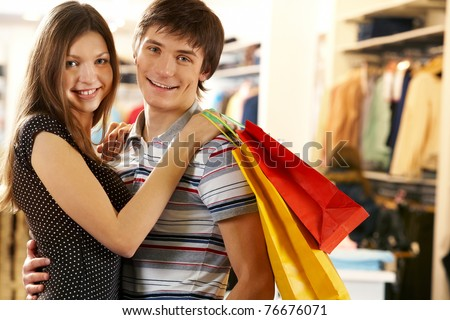 Portrait of joyful husband and wife after shopping looking at camera