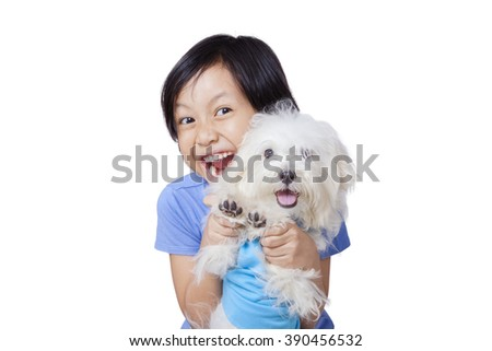 Portrait of joyful little girl playing a maltese dog in the studio, isolated on white background - stock photo