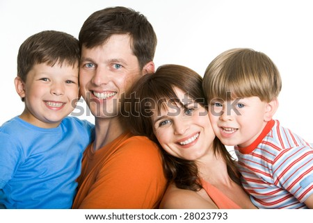 Portrait of joyful parents holding their sons and looking at camera