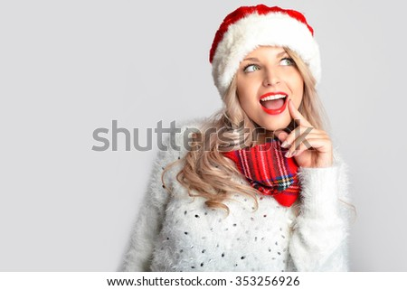 Portrait of joyful pretty woman in red santa claus hat laughing isolated on white background. Beautiful girl looking happy and excited. Happy Christmas and New Year holidays full of fun. - stock photo