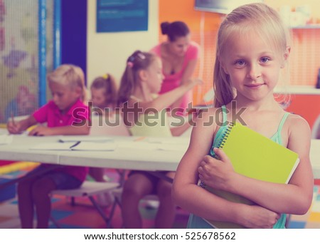 Portrait of joyful smiling  little school girl standing in school class