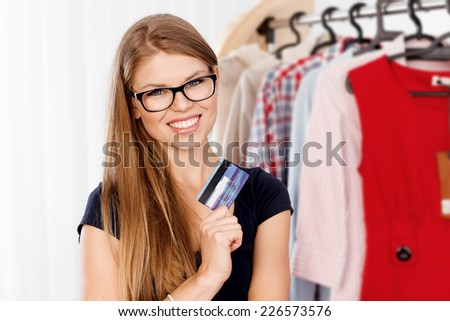 Portrait of joyful woman holding plastic bank card standing in clothes store. Young happy smiling Caucasian female ready for purchases.  - stock photo
