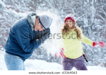 Portrait of joyful woman throwing snowball at man - stock photo