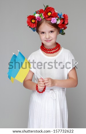 Portrait of joyful young girl in the Ukrainian national clothes on gray background