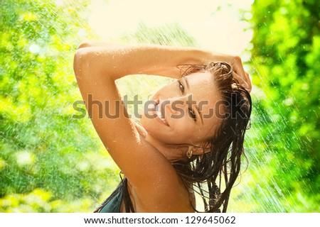 Portrait of joyful young woman under summer rain - stock photo
