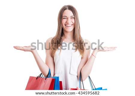 Portrait of joyful young woman with shopping bags holding her hands raised up isolated on white background - stock photo