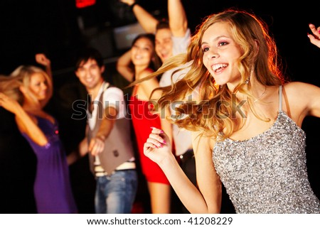 Portrait of joyous girl dancing at party on background of happy teens - stock photo