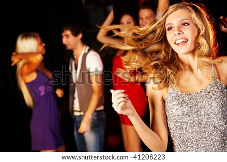 Portrait of joyous girl dancing at party with her friends behind