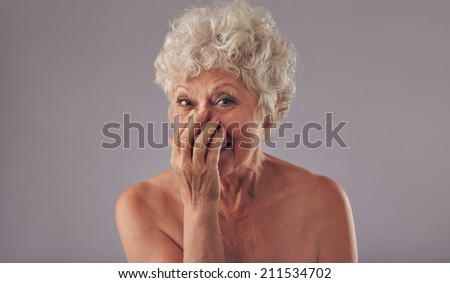 Portrait of joyous senor lady against grey background. Shirtless old woman smiling with hands on mouth. - stock photo