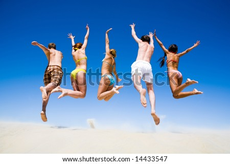 Portrait of jumping young people a backs on the beach - stock photo