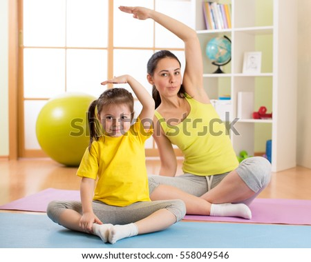 Portrait of kid girl and her mother doing gym exercise at home