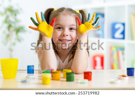 Portrait of kid girl with face and hands painted at home