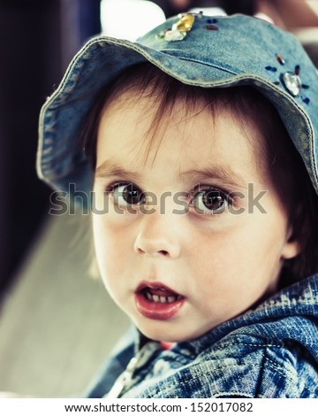 Portrait of kid surprised in the cap. - stock photo