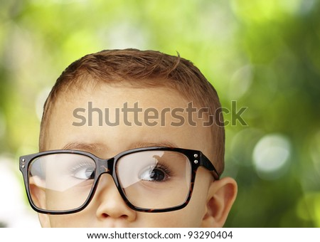 portrait of kid wearing glasses against a nature background - stock photo