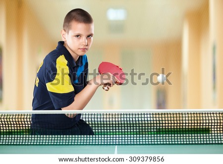 Portrait Of Kid with Racket Playing table Tennis in Action shot - stock photo