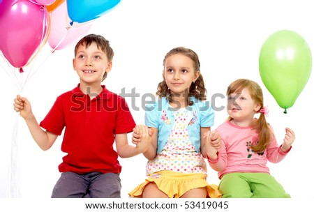 Portrait of kids with colorful balloons looking aside during birthday party - stock photo