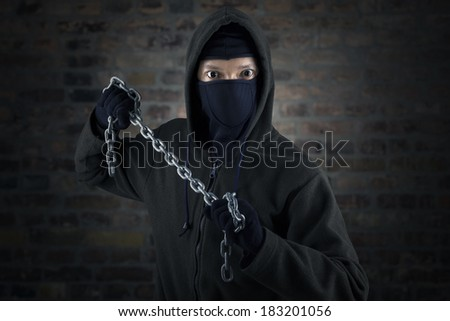 Portrait of killer holding chain in front of brick wall