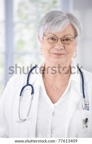 Portrait of kindly smiling senior doctor standing at hospital corridor.? - stock photo