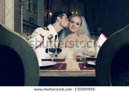 Portrait of kissing bride and groom sitting in a luxurious vintage restaurant. Indoor shot