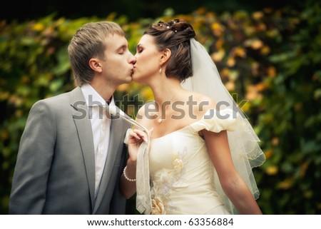 Portrait of kissing newlyweds - stock photo