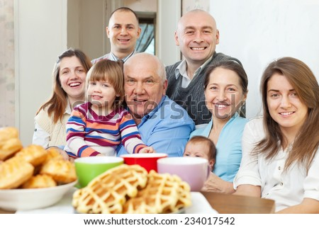 Portrait of large happy three generations family sits on sofa at home together - stock photo