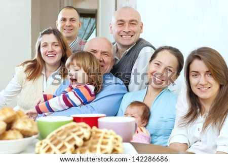 Portrait of  large happy three generations family sits on sofa in livingroom - stock photo