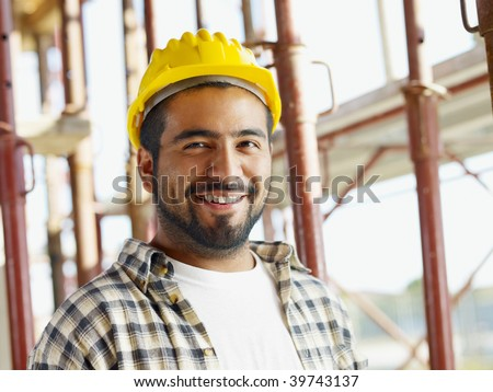 portrait of latin american construction worker, looking at camera - stock photo
