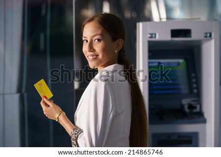 Portrait of latina businesswoman withdrawing dollar from atm cash machine and showing credit card to camera  - stock photo