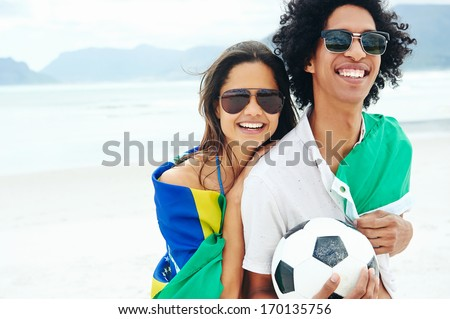 Portrait of latino couple with Brasil flag and soccer ball for world cup
