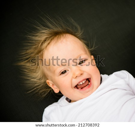 Portrait of laughing baby with standing hair from static electricity - stock photo