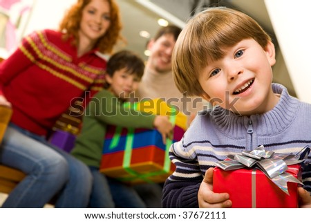 Portrait of laughing boy with nice present on background of his parents and brother