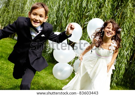 Portrait of laughing children bride and groom with balloons running in park - stock photo