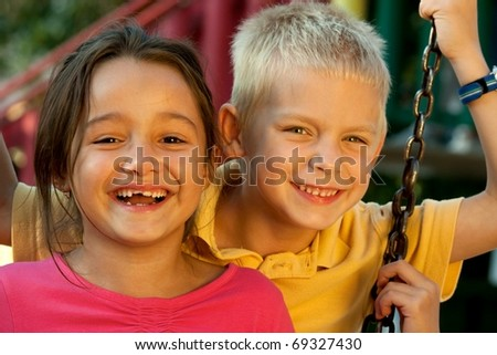 Portrait of laughing children on swing playground outdoors - stock photo