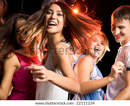Portrait of laughing girl looking at camera while dancing among her friends at disco - stock photo