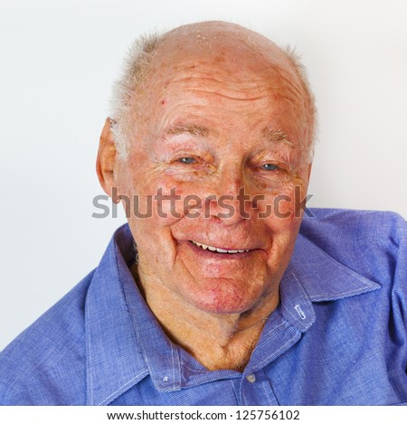 portrait of laughing happy elderly man in front of a white background - stock photo