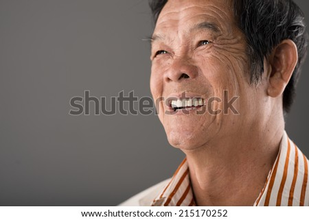 Portrait of laughing senior Vietnamese man - stock photo
