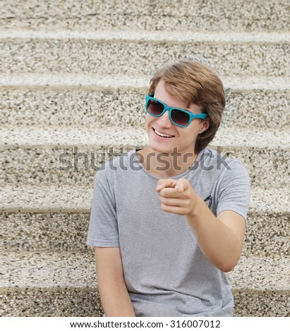 Portrait of laughing teenage boy pointing at the camera. - stock photo