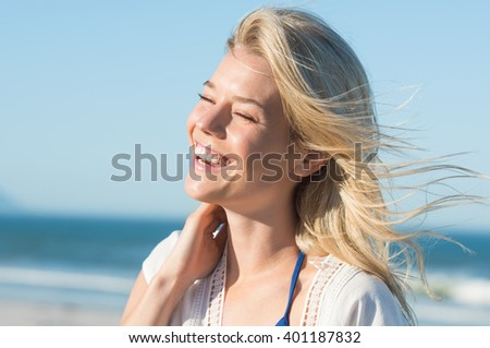 Portrait of laughing woman touching her hair. Cheerful attractive woman enjoying at beach. Joyous woman at sea shore laughing. Young blonde at sea shore with a toothy smile. - stock photo