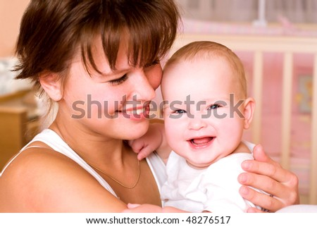Portrait of laughing young mum together with a small daughter in a room interior