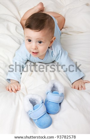 Portrait of little adorable baby boy with shoes