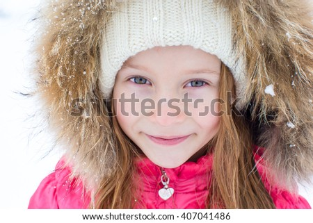 Portrait of little adorable girl in snow winter day - stock photo