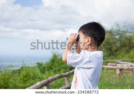 Portrait of little asian boy looking through a  telescope, outdoor in the midst of sun light and sky slightly clouded or fair in holiday - stock photo