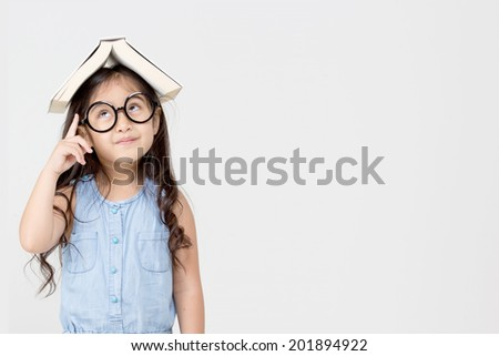 Portrait of little Asian child thinking and put a book on top with copy space