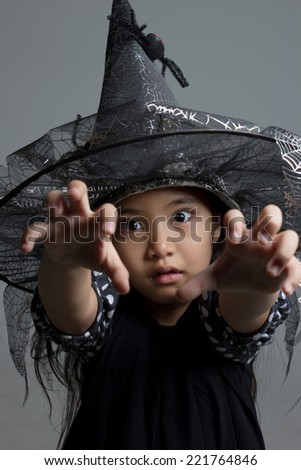 Portrait of little Asian girl in black hat and black clothing - stock photo