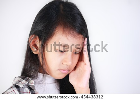 Portrait of little Asian girl with headache touching her head and looking down sadly - stock photo